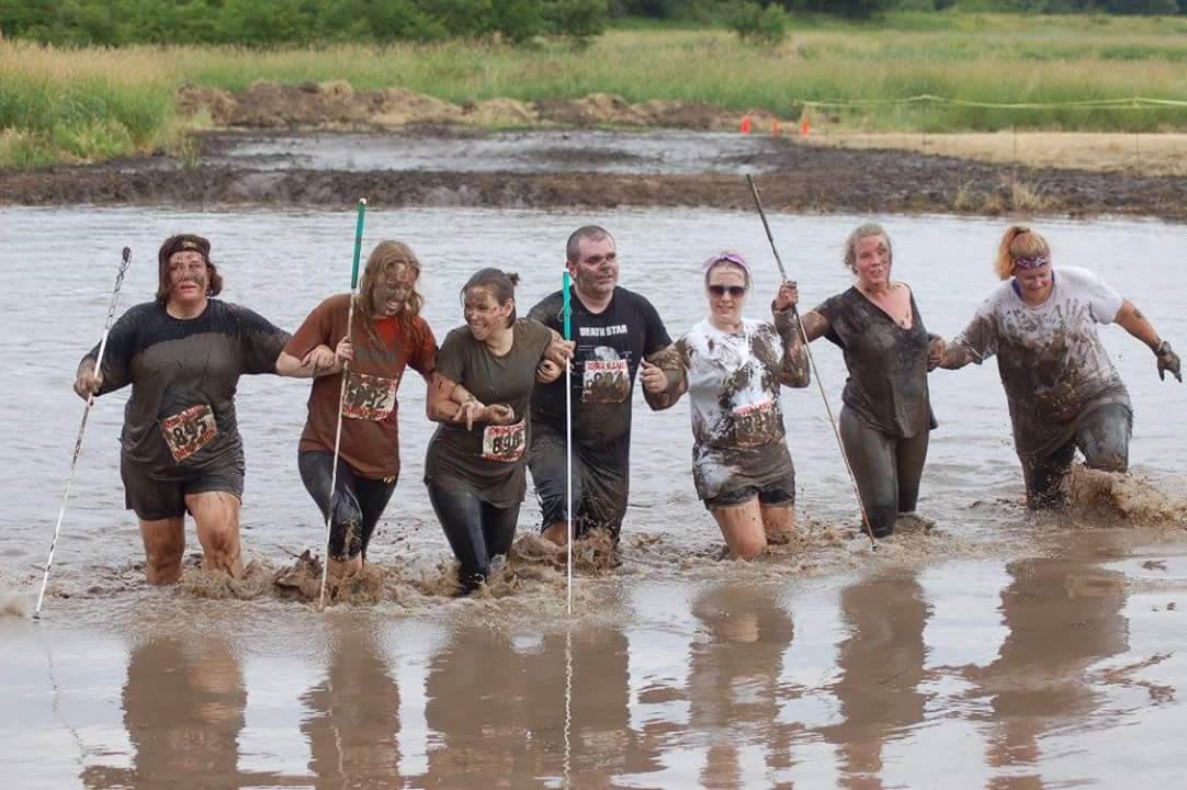 picture of Mud Runners finishing last obstacle Arm in Arm
