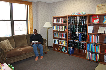 The comfy sofa in the Library lounge area provides a quiet corner for visitor Charles Young to browse the titles available on the bookshelf in the new area.