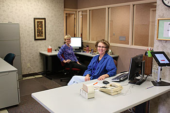 Two helpful staff members of the Iowa Library for the Blind and Physically Handicapped are seen stationed at the newly created information desk area, poised to greet visitors and assist Library patrons with information and circulation needs.