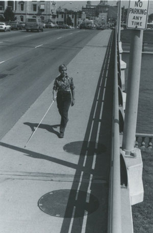 woman with long white cane crossing locust street bridge in Des Moines Iowa circa 1980