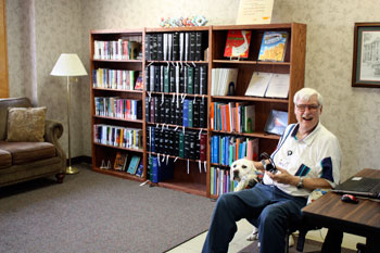 Randolph Anderson with his service dog, Talbot, smiles while using  the computer by the Library's new information desk.