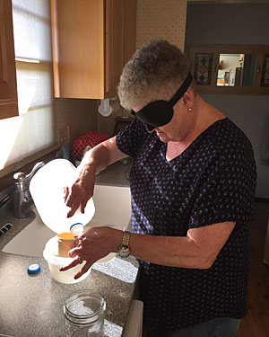 An Iowa Department for the Blind Independent Living program client wears learning shades while using non-visual techniques for measuring ingredients for cooking in her kitchen.