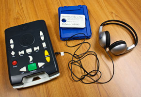 A digital talking book machine with headphones, book cartridge, and NLS mailer