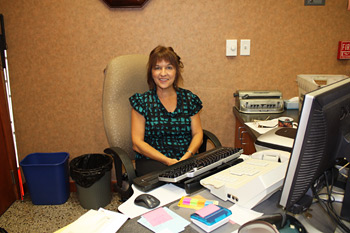 Picture of an employee at her desk after IDB services helped her keep her job