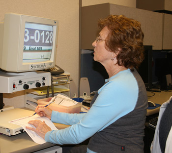 Picture of an employee with a visual impairment using a magnification device to successfully read a form and do her job