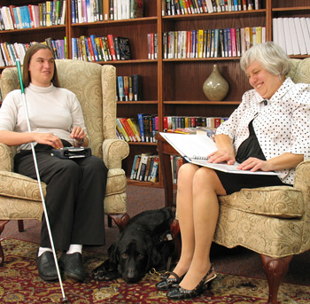 Photo of two library patrons reading a braille and digital audio book together