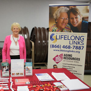 Eileen Creager, LifeLong Links Coordinator, Aging Resources of Central Iowa, 5835 Grand Avenue, Suite 106, Des Moines, Iowa 50312-1444, (515) 633-9535, (800) 747-5352 – toll free, (515) 255-9442 – fax, Please check us out at www.agingresources.com. Eileen is pictured standing at a table exhibit at a vision loss resource fair at the Iowa Department for the Blind in the summer of 2015.